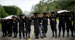 As rain fell, Honduran police officers blocked a road last week in Jacagalpa, near Nicaragua. (Rodrigo Abd/Associated Press)