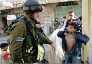 A soldier searches a child in the West Bank